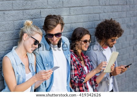 Friends in sunglasses leaning against wall using mobile phone and digital tablet - stock photo