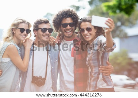 Friends in sunglasses taking selfie on a mobile phone - stock photo