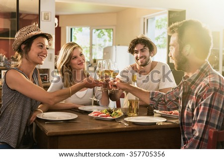 Friends in their 30s having a nice aperitif on a rustic wooden table in a lovely house. They are holding their high glasses of white wine. There are tomatoes mozzarella for starters. Shot with flare