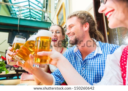 Friends in traditional Bavarian Tracht in restaurant or pub drinking beer in Bavaria, Germany - stock photo