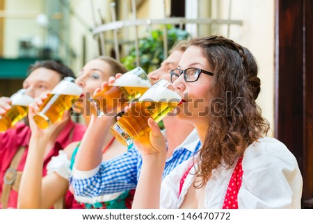 Friends in traditional Bavarian Tracht in restaurant or pub with beer in Bavaria, Germany - stock photo
