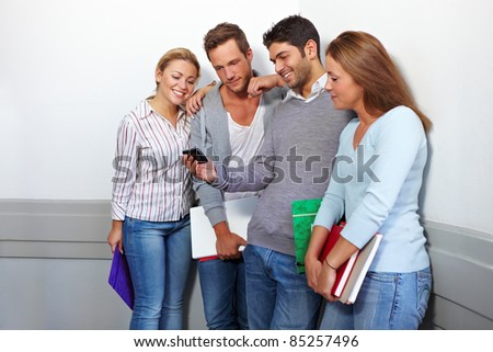 Friends in university looking at a smartphone - stock photo