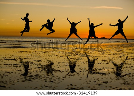 Friends Jumping on the Beach at Sunset - stock photo