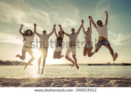 Friends jumping on the beach under sunset sunlight.