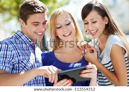 Friends looking at digital tablet - stock photo