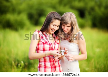Friends looking at photos on digital camera - stock photo