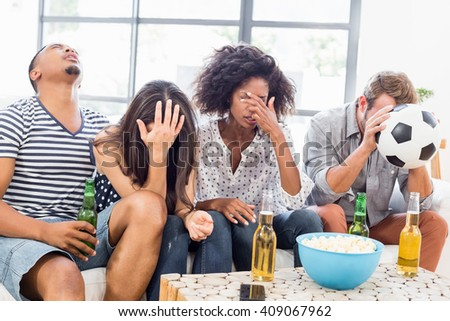 Friends looking upset while watching television in living room - stock photo