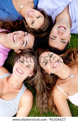 Friends lying down outdoors in a circle and smiling
