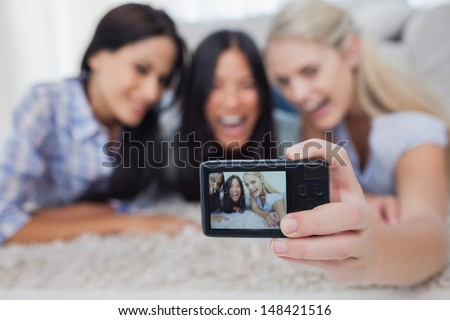 Friends lying on floor and taking a self picture at home in living room - stock photo