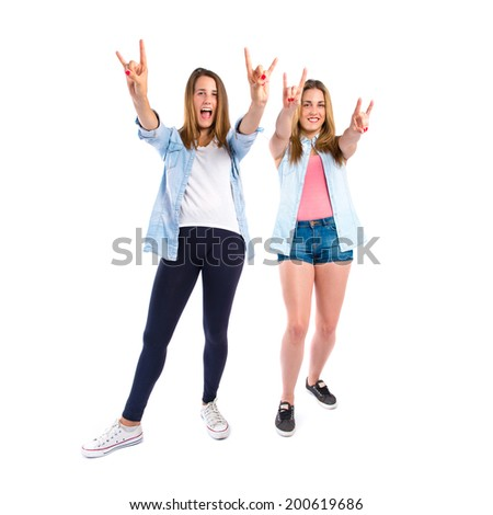 Friends making horn gesture over white background