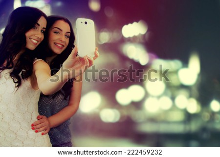 "Friends making selfie. Two beautiful young women making ""selfie""."