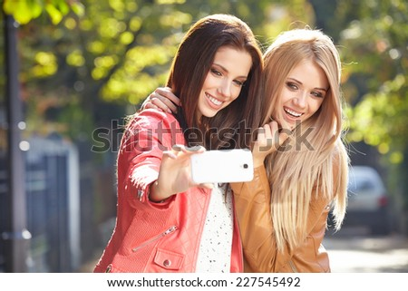 Friends making selfie. Two beautiful young women making selfie and grimacing  - stock photo