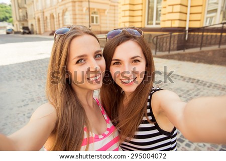Friends making selfie. young women making  selfie and smiling - stock photo