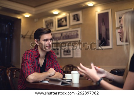 Friends man young woman are having a conversation in the cafe during lunch smiling and expressing some emotions. - stock photo
