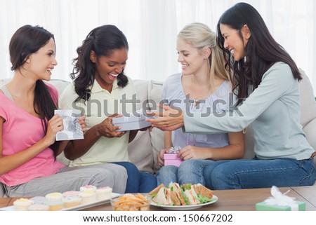 Friends offering gifts to dark woman during party at home on couch - stock photo