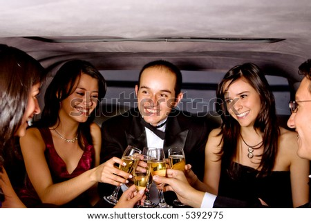 friends on a night out in a limousine with glasses of champagne - stock photo