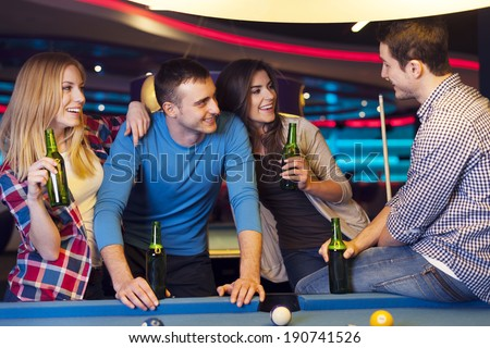 Friends on party in billiard club - stock photo