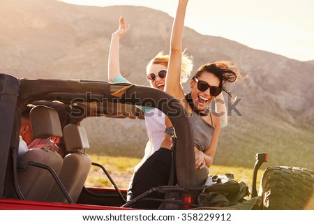 Friends On Road Trip Driving In Convertible Car - stock photo