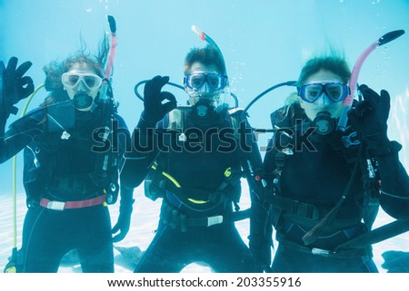 Friends on scuba training submerged in swimming pool looking to camera on their holidays - stock photo