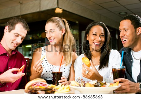Friends - one couple is African American - eating hamburger and drinking soda in a fast food diner; focus on the meal - stock photo