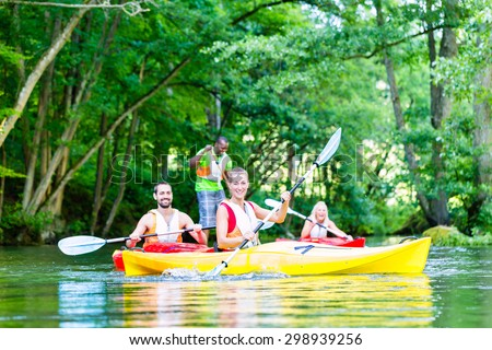 Friends paddling with canoe on forest river - stock photo