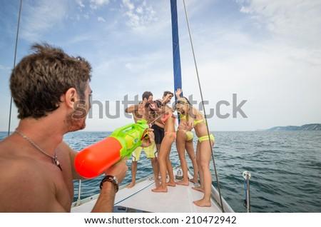 friends play with water guns on the boat - stock photo