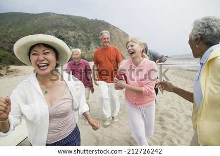 Friends playing american football on beach - stock photo