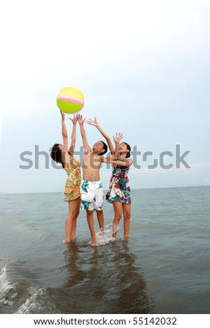 friends playing ball at the beach - stock photo