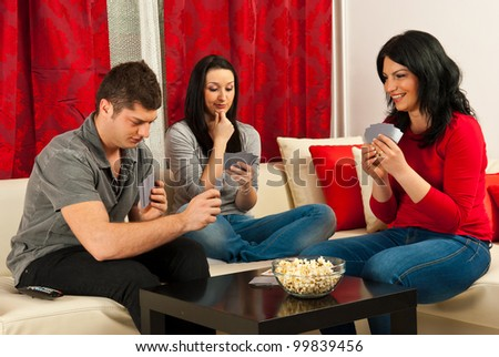 Friends playing cards and sitting together on couch - stock photo