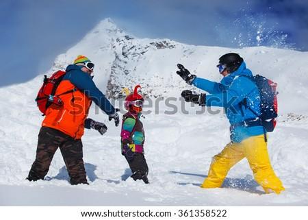 Friends playing snowballs at the ski resort - stock photo