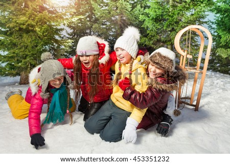 Friends playing together at winter games on snow - stock photo
