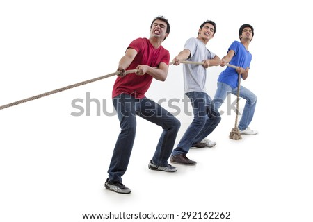 Friends pulling rope together over white background - stock photo