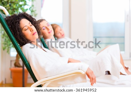 Friends relaxing and sleeping in relaxation room on lounger of wellness spa  - stock photo