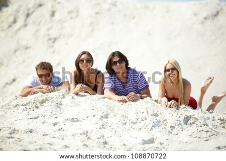 Friends resting on the sand and looking at camera with positive expression - stock photo