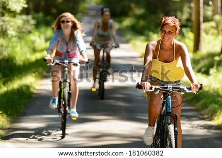 Friends riding their bikes in sunny countryside enjoy sport - stock photo