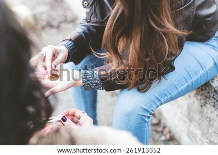 Friends rolling marijuana, ganja,pot or cigarettes closeup - stock photo