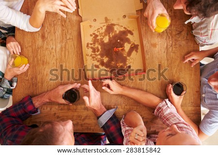 Friends sharing a pizza together, overhead view - stock photo