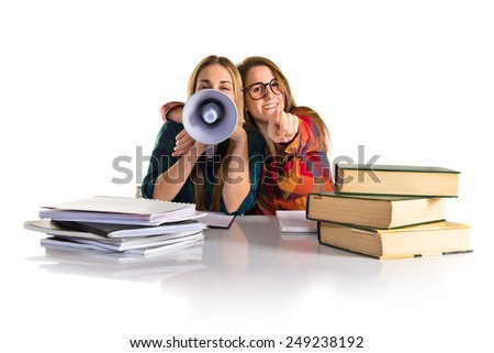 Friends shouting by megaphone while studying - stock photo