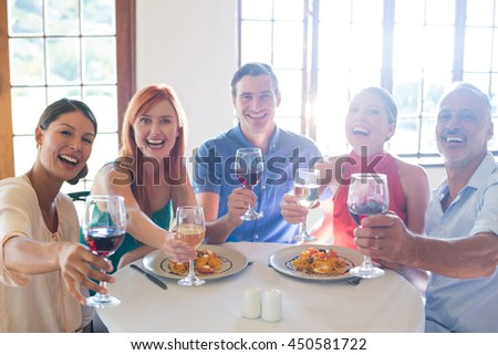 Friends showing wine glass while having meal at restaurant