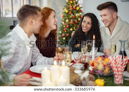 friends sitting around a wooden table and enjoying christmas dinner together - stock photo