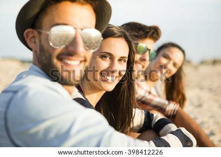 Friends sitting at the beach and having fun - stock photo