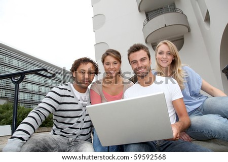 Friends sitting in college campus with laptop computer - stock photo