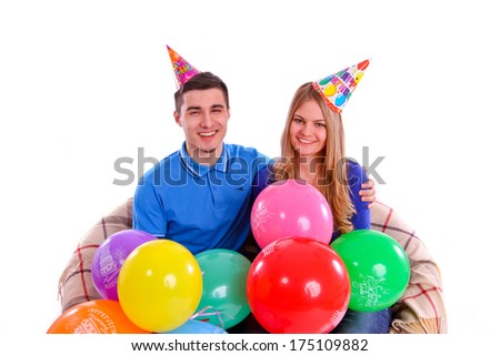 Friends sitting on a sofa with balloons and hats isolated - stock photo