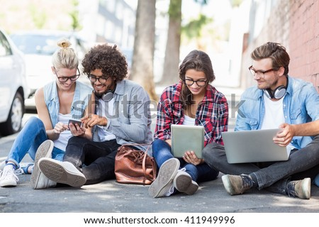 Friends sitting on roadside using mobile phone, digital tablet and laptop - stock photo