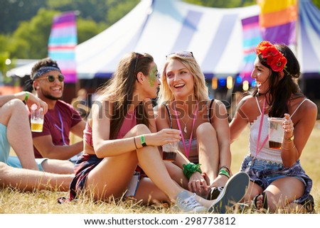 Friends sitting on the grass talking at a music festival - stock photo