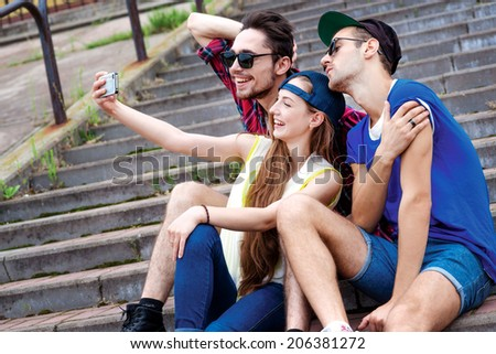 Friends sitting on the steps. Young friends have fun together on the street and smile at each other. Funny guys make Selfie - stock photo
