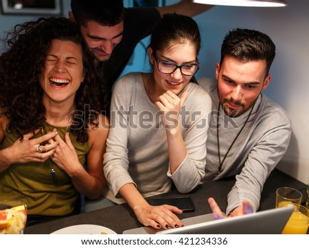 Friends sitting together in living room and watching movie on on laptop and chatting - stock photo