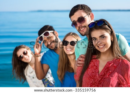 Friends spend a weekend at sea. Beautiful youth smiling. Vacations on the sea. Students are on vacation. Happy people. - stock photo