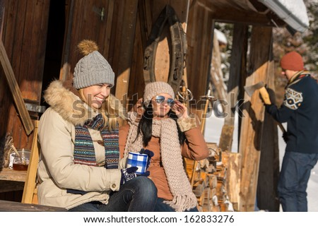 Friends spending winter holiday on mountain cottage enjoy sunny day - stock photo