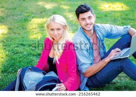 Friends students. Girl-student and male student holding a laptop and books and look at the camera while sitting on the grass near the campus of the University at the break. - stock photo